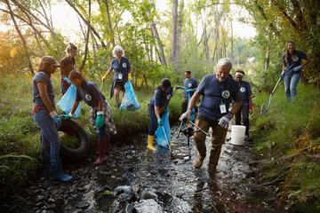 People volunteering, cleaning up garbage in stream
