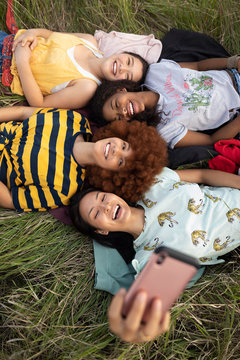 Overhead view teenage girl friends laying in tall grass, taking selfie