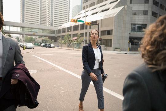 Businesswoman crossing city street
