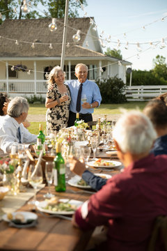 Affectionate couple celebrating anniversary, toasting friends at garden party table