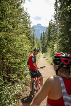 Mature couple mountain biking on sunny forest trail