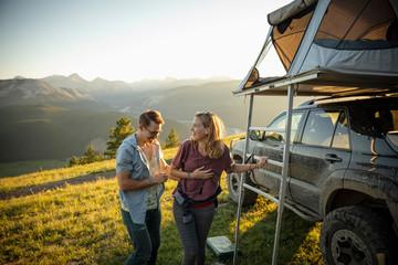 Happy couple climbing into SUV rooftop tent in idyllic mountain field, Alberta, Canada