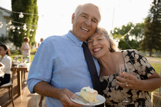 Portrait happy, affectionate couple eating cake and drinking wine, celebrating anniversary at garden party