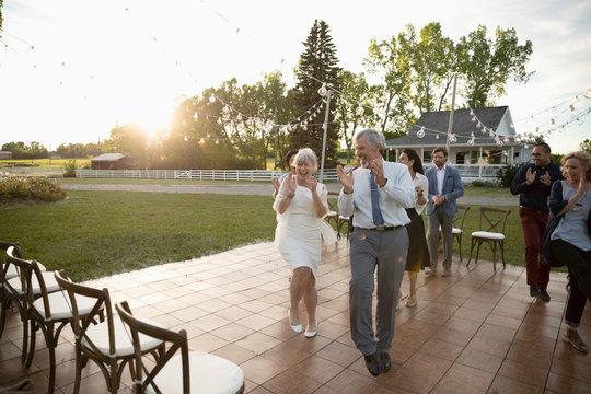 Playful senior bride and groom dancing at wedding reception in rural garden