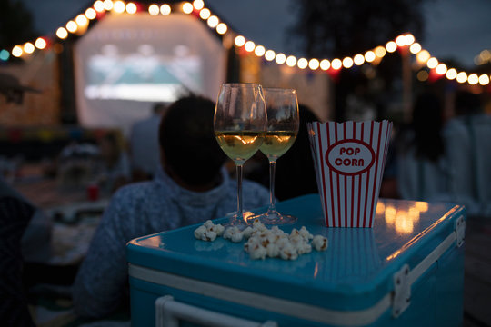 White wine and popcorn on cooler at movie in the park