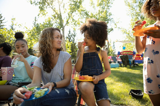 Mother and daughter eating fruit at summer neighborhood block party in park