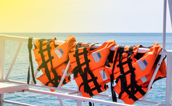 Orange life jacket is a safety device hanging on a steel railings.