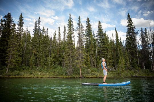 Serene mature man enjoying standing paddleboarding on lake, Alberta, Canada