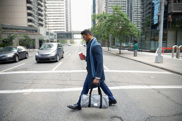 Businessman with coffee and gym bag crossing city street