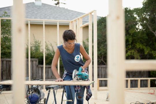Female volunteer using saw, building house