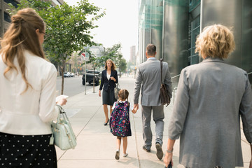 Businessman father and schoolgirl daughter holding hands and walking on urban sidewalk