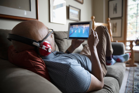 Latinx man with headphones watching sports with digital tablet on sofa
