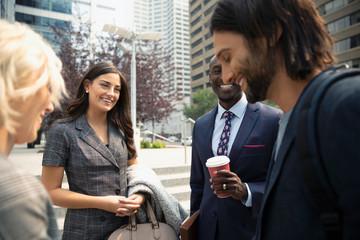 Smiling business people talking on urban sidewalk