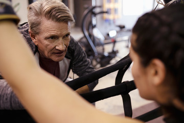 Trainer talking with female boxer in gym