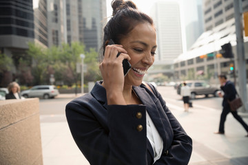 Laughing businesswoman talking on smart phone on city sidewalk