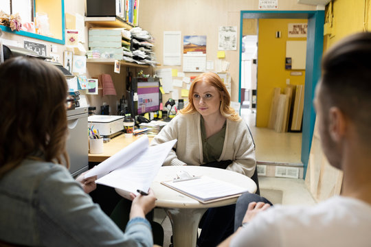 Small business owners interviewing young woman in shop office