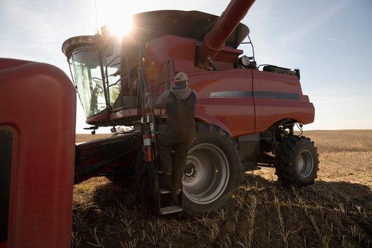 Male farmer climbing into combine harvester on farm