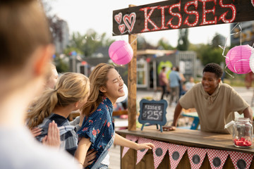 Playful teenage girls at kissing booth