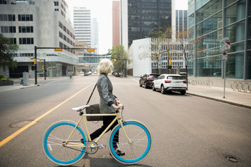 Young businesswoman commuter with bicycle crossing city street