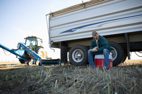 Male farmer eating lunch on cooler near tractor on farm