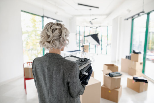 Female fashion designer with stack of jeans in new retail space