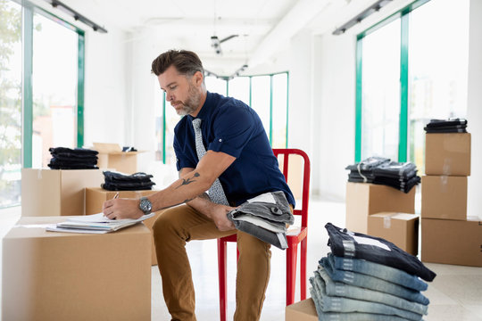 Male business owner checking inventory of jeans in new retail space