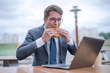business man looking at hamburger in his hands