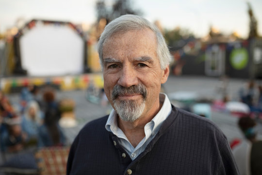 Portrait confident senior man at movie in the park