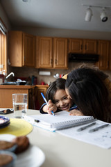 Affectionate mother kissing son doing homework at table