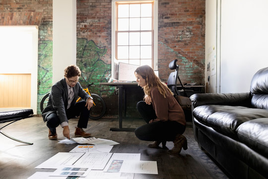 Creative business people reviewing proofs on office floor