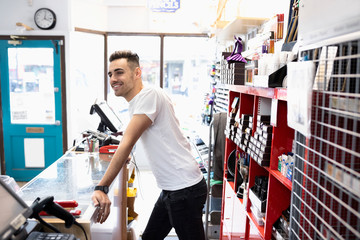 Smiling male business owner working at counter in art supply shop
