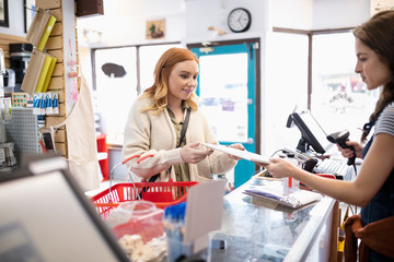 Female business owner helping customer at art supply shop counter