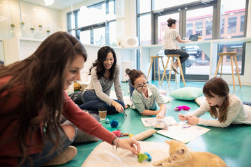 Mothers and daughters drawing and playing with kitten in cat cafe