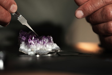 Professional jeweler working with beautiful amethyst at table, closeup