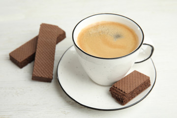 Delicious wafers and cup of coffee for breakfast on white wooden table