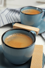 Delicious wafers and coffee for breakfast on table, closeup