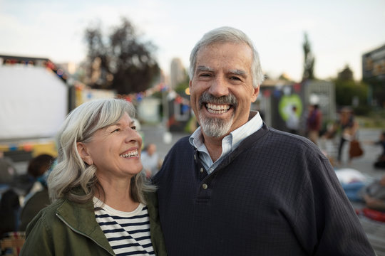 Portrait laughing, carefree senior couple at movie in the park