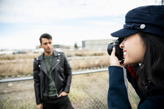 Woman with digital camera photographing man in leather jacket along chain link fence