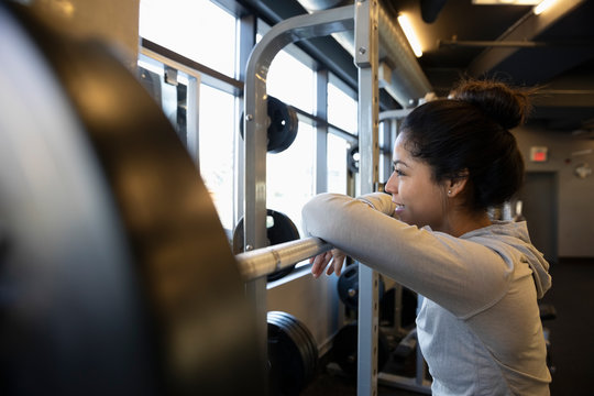 Woman exercising, resting on barbell in gym