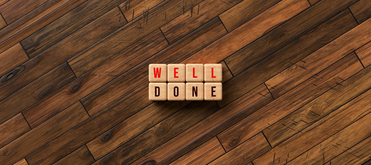 cubes with message WELL DONE on wooden background