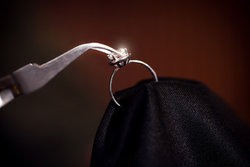 Working with beautiful ring on dark background, closeup. Jeweler's workshop