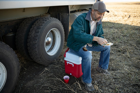 Male farmer eating lunch on cooler on farm