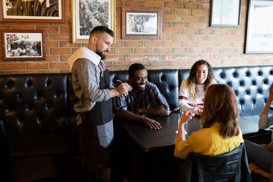 Waiter taking order from friends in bar