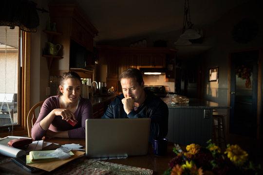 Couple paying bills at laptop in kitchen