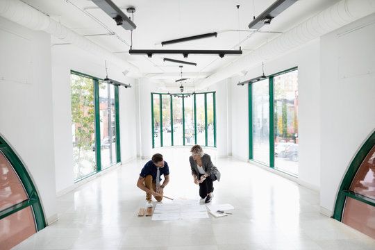 Business people reviewing blueprints in new, empty office space