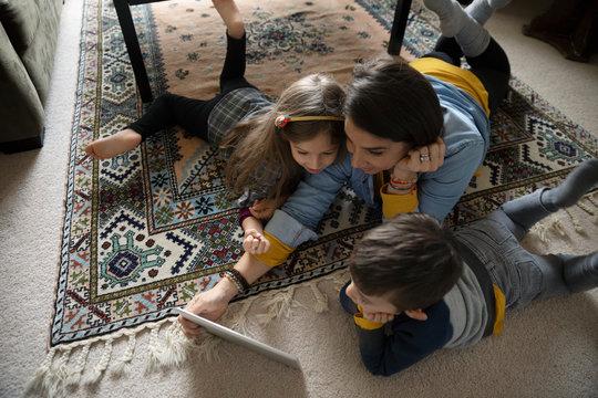 Latinx family using digital tablet on living room floor