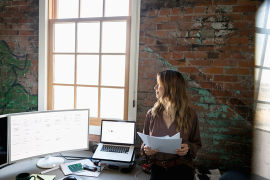 Thoughtful creative businesswoman looking out office window