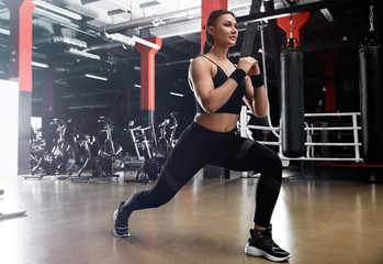 Young woman doing lunges in modern gym