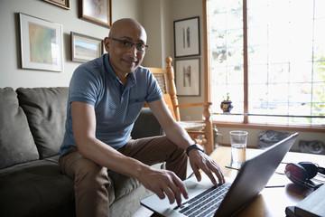 Portrait confident Latinx man using laptop in living room