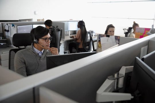 Man with headset working in cubicle at call center